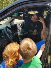 Springettsbury Township Police Officer Cory Landis shows off some of his equipment to some curious children Saturday afternoon at Springettsbury Township Park.