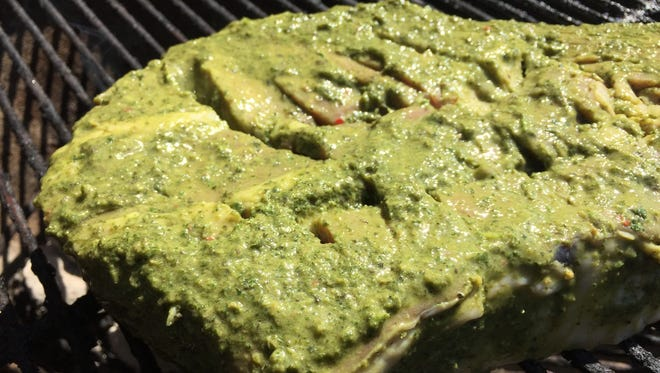 A beef roast marinated in green chimichurri sauce is grilled.