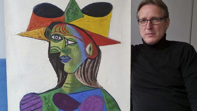 """Dutch art detective Arthur Brand with """"Buste de Femme,"""" a recovered Picasso painting. The painting was stolen from a wealthy Saudi's yacht 20 years ago."""