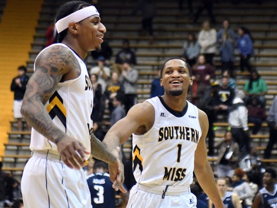 Southern Miss'  Dominic Magee, left, and  Cortez Edwards, right, celebrate after their win in a game against Rice on Thursday in Reed Green Coliseum.