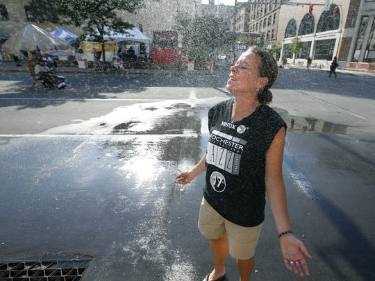 Stephanie Dawson of Greece cools down with a water spray on Chestnut Street during the Xerox Rochester International Jazz Festival.