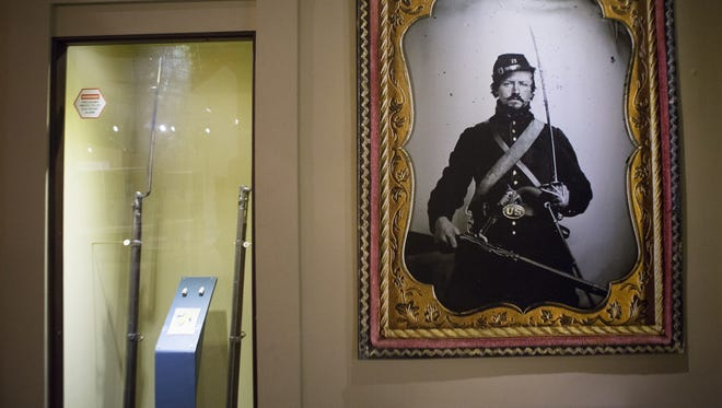 A portrait of a Civil War soldier next to a display of rifles in the Civil War exhibit at the Rochester Museum & Science Center.
