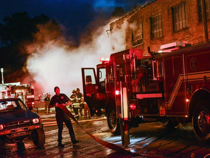 Firefighters battle a structure fire on Banks Avenue in downtown Asheville Tuesday night about 8 p.m. Asheville Fire Department Chief Scott Burnette said the department did not expect any injuries, as it was an abandoned building, and the firefighters were treating it as a defensive fire. 9/9/14