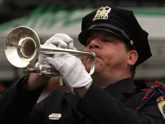 Ben Ihde, a member of the Des Moines Police Honor Guard, plays taps at a service in 20016 honoring those who lost their lives in the 9/11 tragedy five years prior.