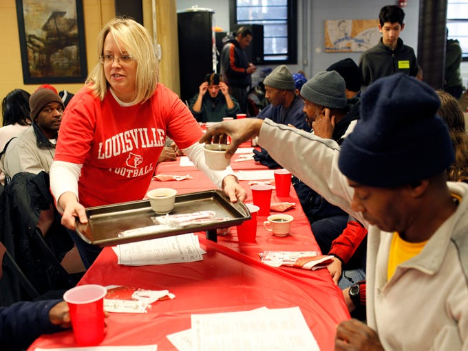 Volunteer Robin Bass, left, serves coffee to members of the homeless community at Jefferson Street Baptist Center during the 5th annual Christmas Eve Brunch for the Homeless. Approximately 100 volunteers and over 200 homeless guests were served brunch, which included biscuits and gravy, pancakes, eggs, ham, bacon and fresh fruit. A service including music, scripture and prayer was held before the meal was served.  Dec. 24, 2013