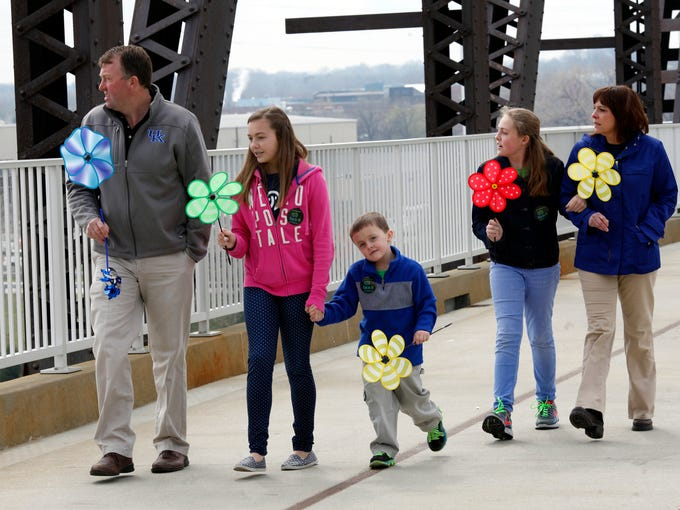 The Brent Family walks across the Big Four Bridge while holding pinwheels during a rally to bring awareness to the victims of child abuse.  This was the kickoff event for Child Abuse Prevention Month organized by the Face It Movement, Kosair Charities and Family & ChildrenÕs Place.  April 8, 2014