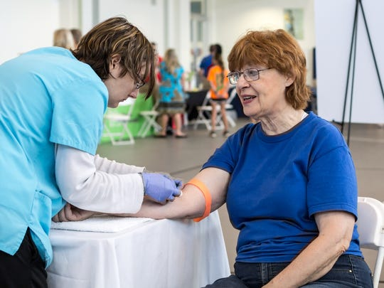 In this file photo, Carolyn Tomlin recieves a venal puncture to test cholesterol and blood sugar levels during the Neighborhood Health Fair at the Lift Wellness Center.