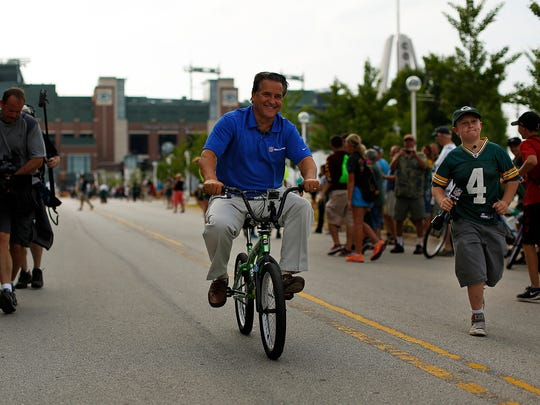 Former NFL head coach Steve Mariucci takes part in the continued training camp tradition by riding a kids bicycle to  training camp practice at Ray Nitschke Field on Monday, Aug. 4, 2014. Evan Siegle/Press-Gazette Media