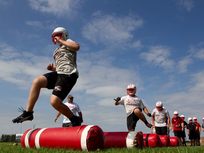 Medford's John Shear, left, leads his teammates in a footwork drill during football practice at Medford Area High School, Tuesday, August 5, 2014.