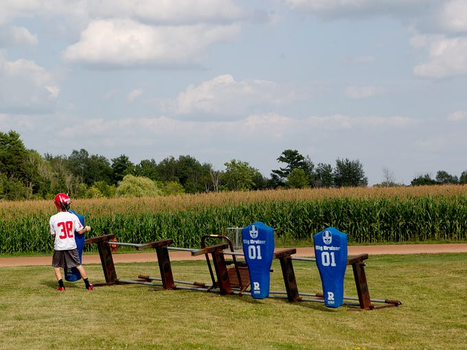 Tim Bauer sets up a blocking dummy on a sled before football practice at Spencer High School, Wednesday, Aug. 6, 2014.