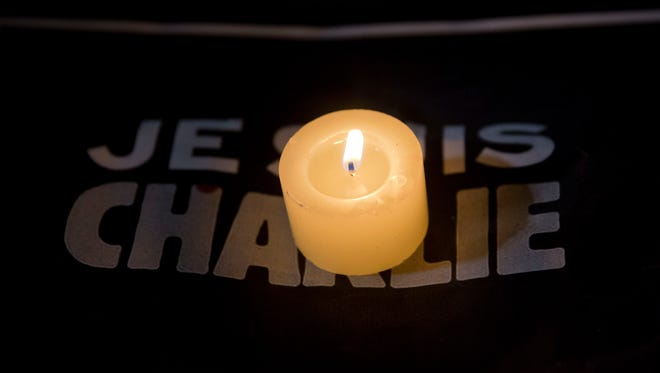 """A candle burns on a sign that reads in French """"I am Charlie"""" during a gathering in Sao Paulo, Brazil."""