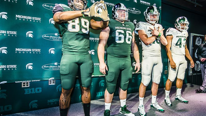 Shilique Calhoun ,from left, Jack Allen, Connor Cook and Ed Davis model new MSU Football uniforms Thursday April 23, 2015 at the Izzo Family Center in Spartan Stadium.