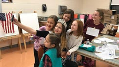 Alexa Daley poses for a selfie with younger girls.
