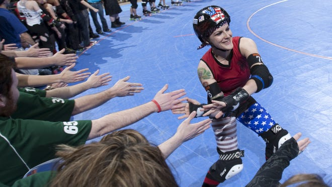 Maiden America (Melissa Smith), slaps hands during player introductions in the evening's Naptown Roller Girls main event at Bankers Life Fieldhouse, Indianapolis, Friday, April 20, 2012. NRG's Tornado Sirens beat the Tampa Bay Tantrums 149-126.