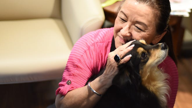 Lucy Zandol pets her dog on Tuesday, April 21, 2015, at First American Title Company in Salem, after participating in the Oregon Humane Society's Biscuit Challenge.