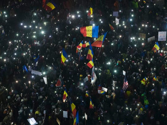 Protesters wave flags as they gather outside the government building in Bucharest, Romania, Thursday, Feb. 9, 2017. Romania's justice minister resigned Thursday following mass protests over a law that eases criminal penalties for government officials engaged in corruption.