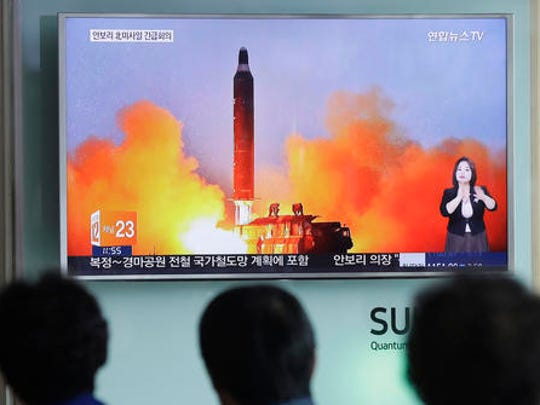 FILE - In this June 23, 2016, file photo, people watch a TV news channel airing an image of North Korea's ballistic missile launch published in North Korea's Rodong Sinmun newspaper at the Seoul Railway Station in Seoul, South Korea.