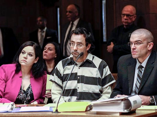 Dr. Larry Nassar, center, and his attorneys, Shannon Smith and Matt Newburg, listen to Judge Donald Allen Jr. rule that Nassar, a former Michigan State University and USA Gymnastics sports doctor, should stand trial on sexual assault charges during a hearing, Friday, Feb. 17, 2017, in Lansing, Mich. Nassar is accused of assaulting a girl from the age of 6 until the girl was 12 at his home in Holt, Mich. He's pleaded not guilty.