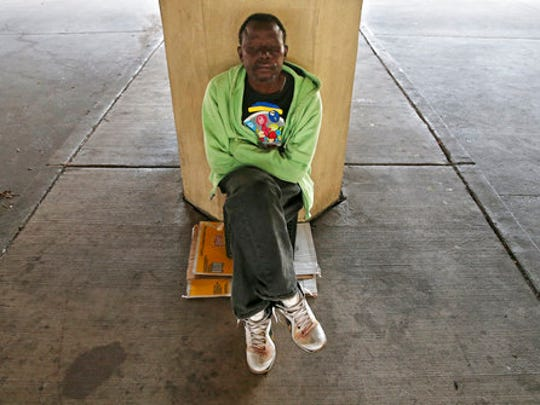 In this April 11, 2017 photo, William Hardy, who is homeless, poses for a portrait where he sleeps with a crate and a cardboard box under the Pontchartrain Expressway, in New Orleans. Hardy was given a camera and his works are part of an exhibit by artists, who are or were previously homeless, currently on display at LeMieux Galleries in New Orleans' Arts District.