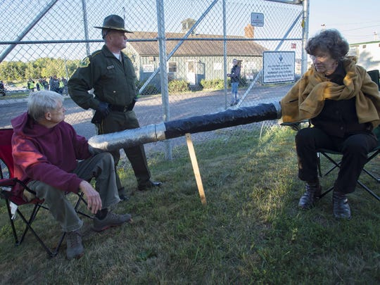 Douglas Smith, left, and Ulrike von Moltke, right, both of Sharon, are two of six protesters who chained themselves together at the Williston construction site for the Vermont Gas pipeline on Monday, September 21, 2015.  Lt. Garry Scott of the Vermont State Police was on hand to assist Smith, who is legally blind, after he was cut free and arrested.