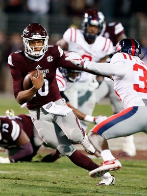 Mississippi State quarterback Keytaon Thompson (10) runs for a first down past Mississippi defensive back A.J. Moore (30).