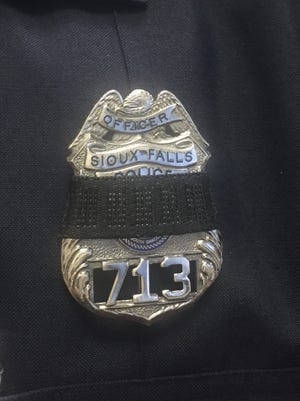 Sioux Falls police spokesman Sam Clemens wears a mourning band around his police badge to show support for two officers who were killed in Des Moines on Wednesday, Nov. 2, 2016.