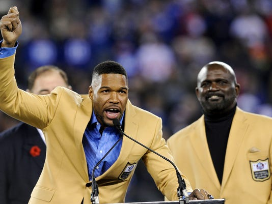Pro Football Hall of Fame defensive end Michael Strahan, left, speaks after he received his Hall of Fame Ring of Excellence as Lawrence Taylor watches him during a halftime ceremony of an NFL football game between the New York Giants and the Indianapolis Colts, Monday, Nov. 3, 2014, in East Rutherford, N.J.  (AP Photo/Bill Kostroun)