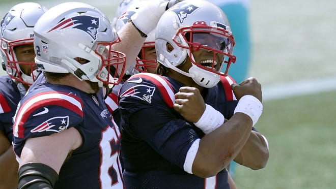 New England quarterback Cam Newton celebrates the first of his two rushing touchdowns in Sunday's win over Miami.