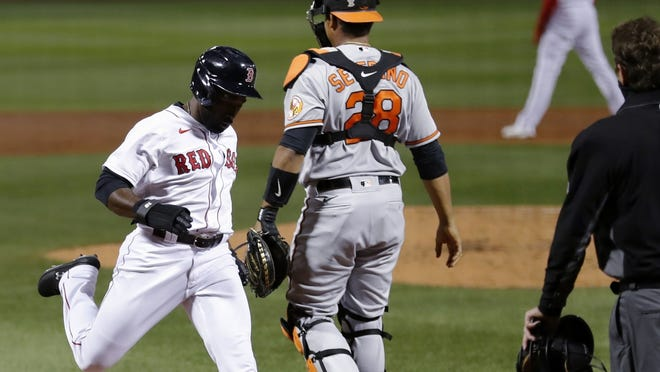 Boston's Jackie Bradley Jr. scores next to Baltimore's Pedro Severino on a sacrifice fly by Michael Chavis during the second inning of Tuesday's game.