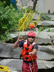 Lt. Scott Barnes thrwos a rescue rope during the tuesday training.