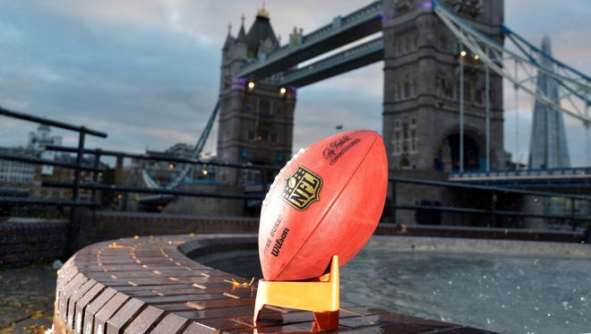 A NFL Wilson official football sits with the Tower Bridge and River Thames in the background.