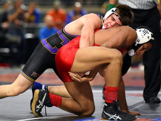 Fort Pierce Central's Jared Fieitas (top) wraps up