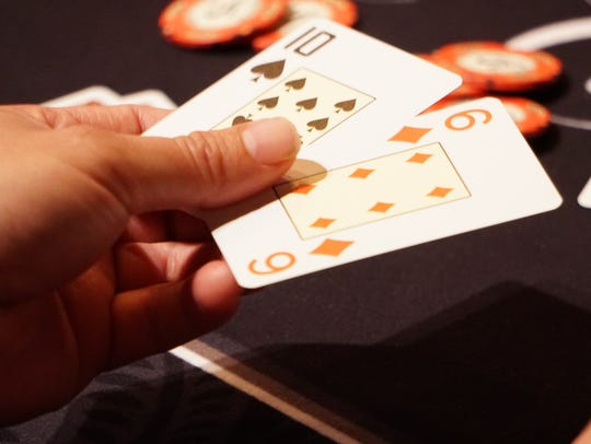 Paul Espinoza shows his cards during a game of Texas