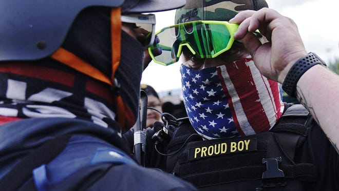 """A member of the Proud Boys, right, stands in front of a counter protester as members of the Proud Boys and other right-wing demonstrators rally on Saturday, Sept. 26, 2020, in Portland. President Donald Trump didn't condemn white supremacist groups and their role in violence in some American cities this summer. Instead, he said the violence is a """"left-wing"""" problem and he told one far-right extremist group to """"stand back and stand by."""""""