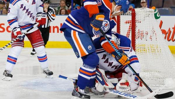 New York Rangers goaltender Henrik Lundqvist (30) makes a save on Edmonton Oilers forward Matt Hendricks (23) during the second period Sunday at Rexall Place.