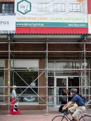 """Pedestrians walk past 608 Market St., a residential project, in downtown Wilmington, on Wednesday. """"Every year, I think, it gets better and better,"""" says downtown resident Samantha Connell, 28."""