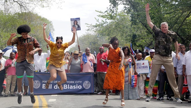 """New York Mayor Bill de Blasio, right, and his children, Dante, left, and Chiara, second left, and wife, Chirlane McCray, do the """"Smackdown"""" dance move as they march in the West Indian Day Parade, Monday, Sept. 1, 2014, in the Brooklyn borough of New York. (AP Photo/Mark Lennihan)"""