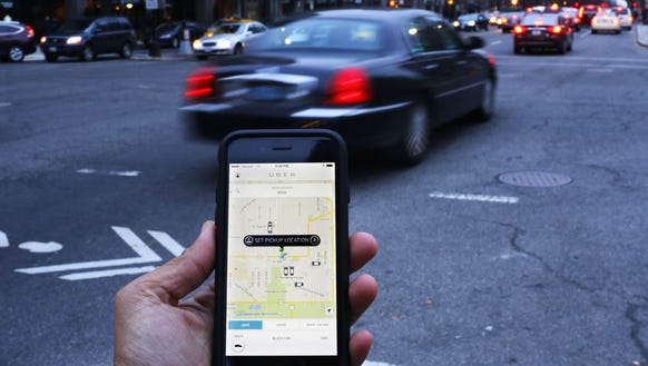 A file photo shows an Uber app as cars drive by in