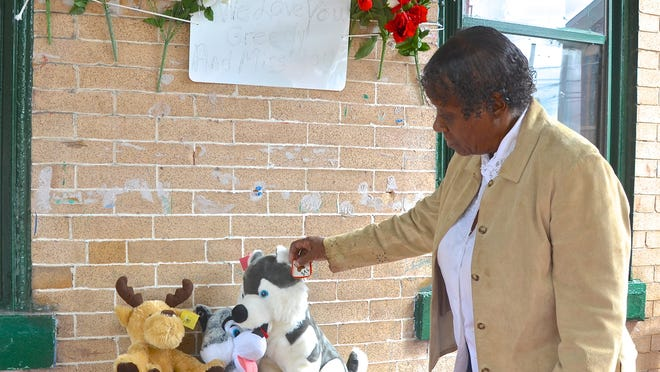 Dianna Jones, 70, creates at memorial for her dog, Greedy, outside her family's home in Camden. The animal was shot and killed the morning of Aug. 7.