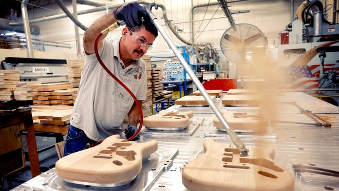 Fender Stratocaster bodies are cleaned out after being cut down by Manuel Espinoza at the Fender factory in Corona, Calif.