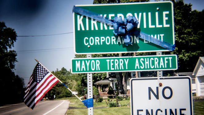 A blue ribbon is tied May 16, 2017, to a Kirkersville, Ohio, city-limit sign about half a mile outside downtown in remembrance of the shooting victims in the May 12, 2017, attack in which the ex-boyfriend of a nurse at Pine Kirk Care Center killed her, a nurse's aide and the village police chief before killing himself.