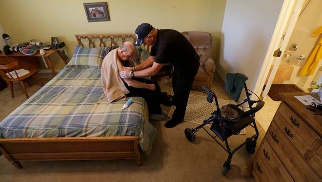 Caregiver Warren Manchess washes Paul Gregoline, in Noblesville, Ind., on Nov. 27, 2013.