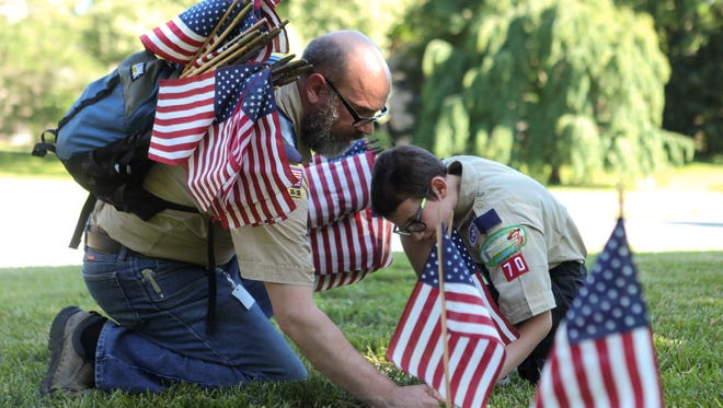 Thomas Becker and Barret Becker of Cub Scout Pack 70 from Fort Thomas, Kentucky, place flags on the graves of soldiers on Thursday, May 24, 2018, in Spring Grove Cemetery, Cincinnati.