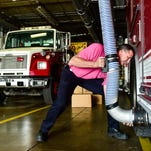 Ty Williams of the First Consolidated Fire District in Caledonia demonstrates how a special exhaust system sucks fumes out of the garage where fire trucks are stored.