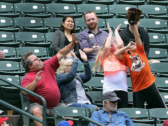 Fans at Frontier Field protect themselves as they try to catch a foul ball.