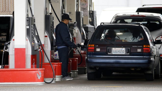 FILE - In this Wednesday, May 6, 2015, file photo, cars line up as an attendant pumps gas at a station in Portland, Ore. With more money in their pockets thanks to lower gas prices and an improved job market, AAA expects more than 37 million Americans to travel for Memorial Day, the most since 2005. (AP Photo/Don Ryan, File)