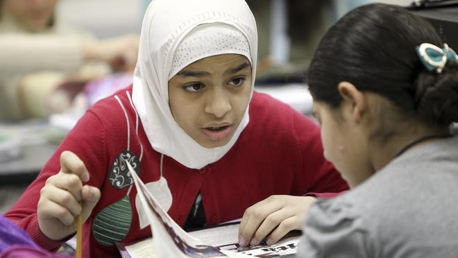 Shaheed Sami, left, works with Maryuri Quijada Martinez on a writing exercise at the ESL Newcomer Academy at the former Myers Middle School. The ESL Newcomer Academy added the Myers satellite campus as an influx of immigrant students has entered the school system. The academy helps students assimilate.March 3, 2015
