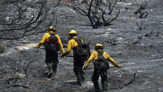 Firefighters make their way up a charred hillside, while battling the Washington Fire on June 23 in the Sierra Nevada Mountains near Markleeville, Calif.