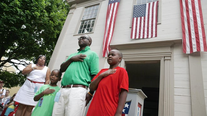 Rodney Tull Sr., center, leads the Pledge of Allegiance with his sons, Zion Tull, left, and Rodney Tull Jr., right, after he was naturalized as an American citizen with a group of thirty people from sixteen different countries in a ceremony at the Genesee Country Village & Museum on Independence Day. Tull Sr. is from Barbados.