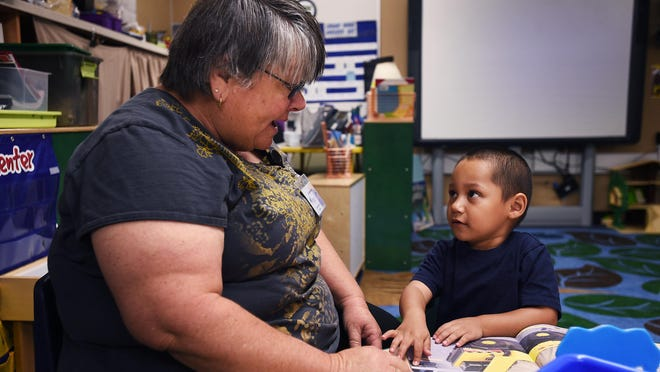 Teacher Lory Rehne reads a book with pre-kindergarten student Junior Alvarez at Booth Elementary School in Reno on Aug. 27.